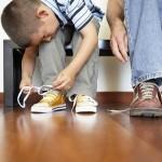 Kleiner Junge bindet sich die Schuhe