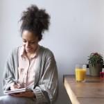 Frau sitzt am Küchentisch und schreibt