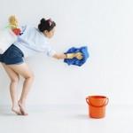 Eine junge Frau wischt die Wand mit einem Lappen ab