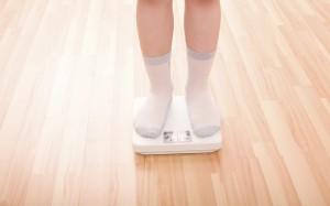 Übergewicht: Junge steht auf einer Körperwaage