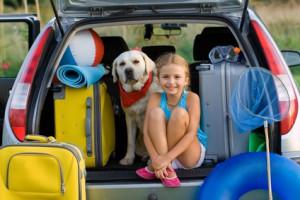 Mädchen mit Hund im Kofferraum